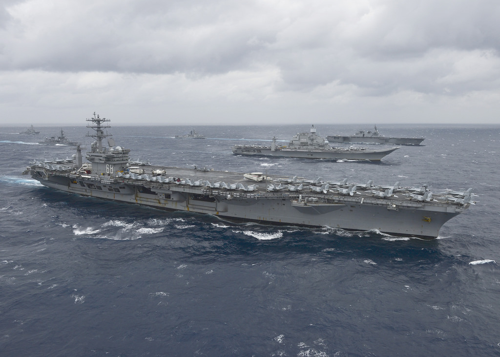 USS Nimitz leads a formation of ships photo
